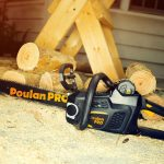Poulan Pro Chainsaw laid on floor next to cut wood