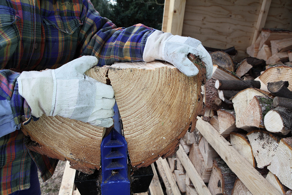 Large log being guided through a log splitter